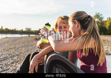 Großmutter und Enkelin eine Pause nach dem Training am Fluss - Stockfoto