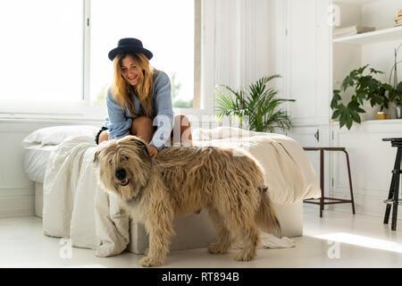 Lächelnde junge Frau sitzt auf dem Bett streicheln ein Hund - Stockfoto
