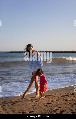 Mutter und Tochter zu Fuß am Strand, Hand in Hand - Stockfoto