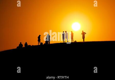 Ein schönes Bild von Menschen warten auf den Sonnenuntergang am Rand der Düne (Rot Sand dune) mit orange Himmel Hintergrund im Sommer in Mui Ne, Vietnam - Stockfoto
