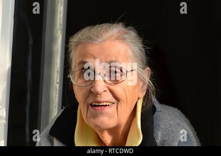 Porträt der fröhliche, gesunde alte Dame mit Brille schauen durch Fenster - Stockfoto