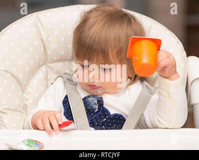Cute Dirty Little Girl essen Joghurt mit Plastiklöffel, während in den hohen Stuhl am Tisch in der Küche. Bild mit selektiven Fokus. - Stockfoto