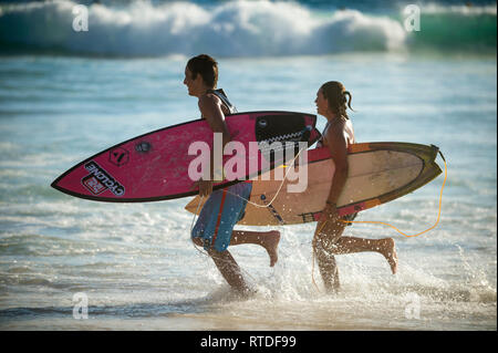 RIO DE JANEIRO - Februar 9, 2017: Ein paar Surfer mit Surfbrettern über die Wellen an Arpoador, der beliebten Surf Pause am Strand von Ipanema. - Stockfoto