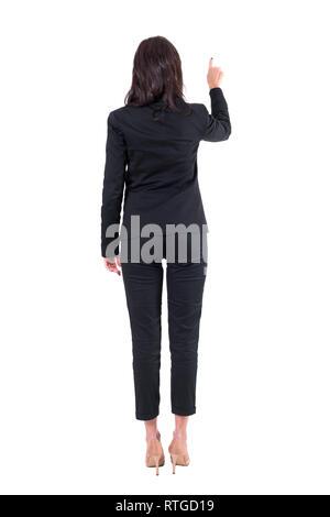Ansicht der Rückseite des eleganten Business Frau im schwarzen Anzug, mit interaktivem Touchscreen button Finger. Voller Körper auf weißem Hintergrund. - Stockfoto