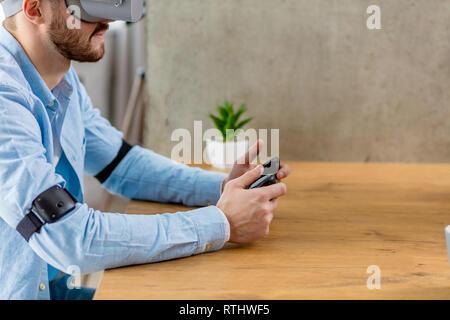Junge kaukasier männlich Designer tragen Virtuelle Realität Gerät, Controller in der Hand, neue virtuelle Projekt, Seitenansicht business casual s - Stockfoto