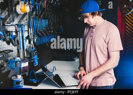 Thema business Beruf Manager und Technologie. Junge stilvolle Kaukasier Männlich Eigentümer Fahrrad Shop verwendet ein Laptop in der Nähe der Stand mit den Tools - Stockfoto