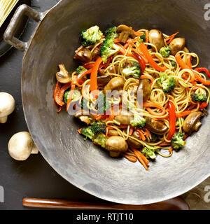 In der Nähe von udon unter Rühren braten, Nudeln mit Gemüse im Wok Pfanne auf dunklem Hintergrund. Rühren, gebratenes Gemüse mit Nudeln im asiatischen Stil. Ansicht von oben, l - Stockfoto