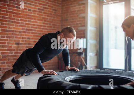 Kaukasische crossfit männlichen Trainer zeigt crossfit plyometric Push-up-Technik, auf LKW-Reifen zu seinem weiblichen Auszubildenden durchgeführt, ihre Förderung mit seinem ow