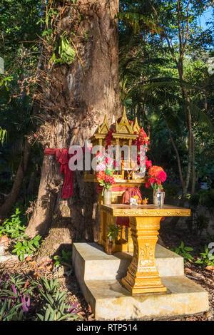 Geist Haus in Thailand mit Blumengirlanden in der Nähe der Großen Baum - Stockfoto