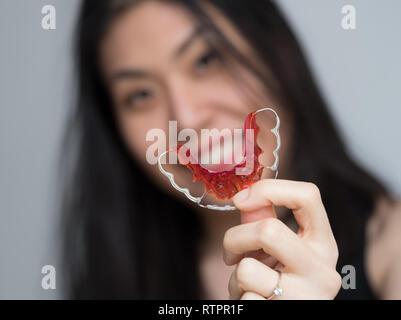 Porträt der schönen asiatischen Patienten Frau mit kieferorthopädischen Halterungen in der zahnmedizinischen Klinik, lächelnde Mädchen mit blauen Halterung, Spange für die Zähne. - Stockfoto