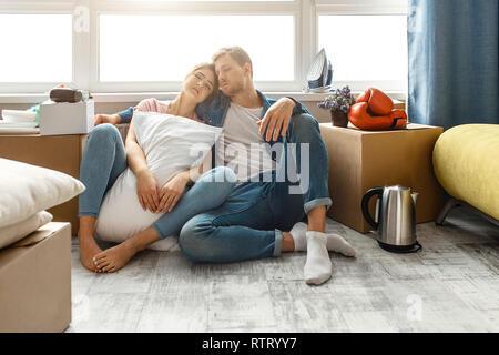 Junge Familie Paar gekauft oder Ihre erste kleine Wohnung gemietet. Die Leute sitzen auf dem Boden und Schlafen. Müde und erschöpft. Verschieben Sie es auspacken. Junge Frau ho - Stockfoto