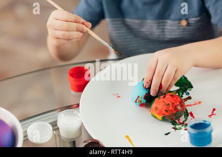 Hausgemachte Ostern Dekorationen und kleinen Helfer. Selektiver Fokus der kleinen Hände eines Jungen, gekochte Eier mit bunten Farben auf weißem Schild - Stockfoto