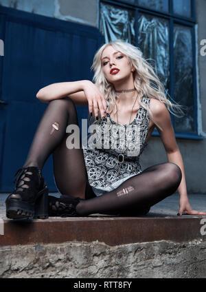Schöne junge Grunge (Rock) Mädchen in einem Kleid und zerrissene Strumpfhosen rauchen Zigarette. Street Portrait von informellen Modell. - Stockfoto