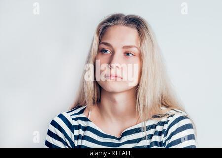 Junge schöne traurige Frau ernst und Betroffenen zur Seite schauen und nachdenklichen Gesichtsausdruck, Gefühl auf weißem Hintergrund gedrückt. Negative emotio - Stockfoto
