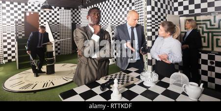 Nachdenklich afrikanischen Geschäftsmann in der Nähe von Schachbrett auf der Suche Zimmer mit Kollegen, die versuchen, die Lösung der Rätsel zu finden. Herausforderung, Lösung Konzept - Stockfoto