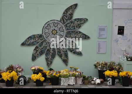 Grenfell Memorial Artwork: Gnade, Liebe, Hoffnung, Einheit, Mut, Brücken, zusammen. Blumen sind unter einem schönen Stück Kunst, die Blütenblätter. - Stockfoto