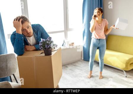 Junge Familie Paar gekauft oder Ihre erste kleine Wohnung gemietet. Müde, gelangweilt Mann sieht erschöpft. Junge Frau stehen und reden am Telefon. Bewegen in und - Stockfoto