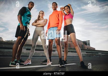 Volle Länge des gemischten Rennen Freunde stehen draußen auf der Straße nach dem Workout. Fitness Gruppe gemeinsam nach dem Workout. Low Angle Shot. - Stockfoto