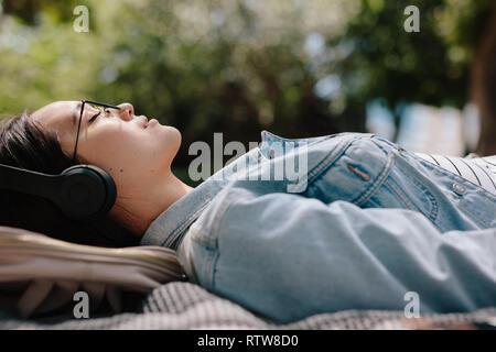 Seitenansicht einer Frau Entspannung im Freien Musik hören, Kopfhörer tragen. Nahaufnahme einer jungen Frau draussen schlafen in einem Park das milde genießen