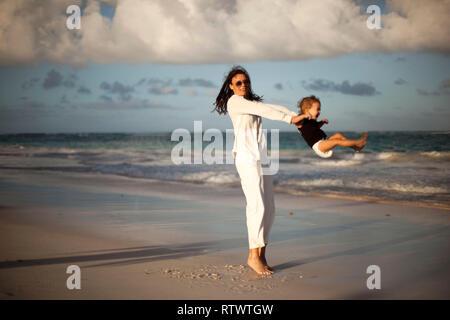 Mutter und Tochter Spaß am tropischen Strand-Mama das Spielen mit Ihrem Kind im Urlaub neben dem Ocean - Familie Lebensstil und Liebe Konzept