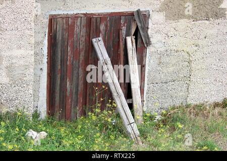 Verlassenes Haus Wand mit alten gerissenen Holztür Garagentore mit Risse im Lack überzogen und mit Holzbrettern mit ungeschnittenem Gras umgeben unterstützt. - Stockfoto