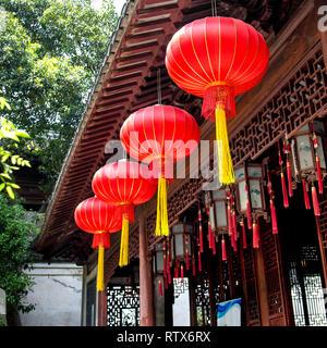 Helle rote Laternen mit gelben Quasten hängen vom Dach in den Yu Garten, das alte Shanghai, China. - Stockfoto