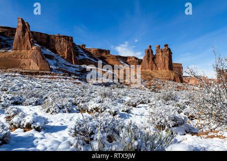 Drei Klatschbasen feature mit Schnee auf dem Boden und blauer Himmel im Arches National Park - Stockfoto