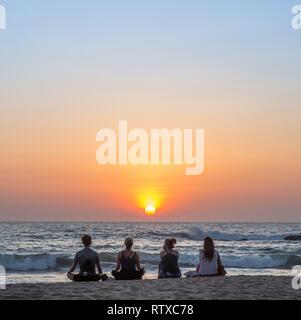 Die Leute am Strand bei Sonnenuntergang in Agonda, Goa, Indien.