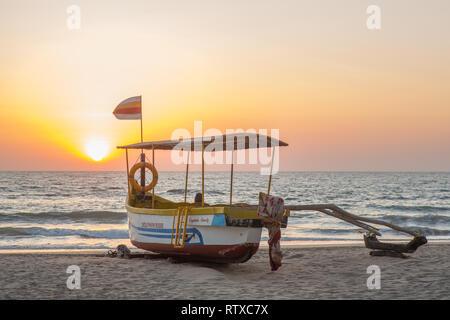 Ein Delphin Kreuzfahrt Boot auf den Strand von Agonda in Indien bei Sonnenuntergang