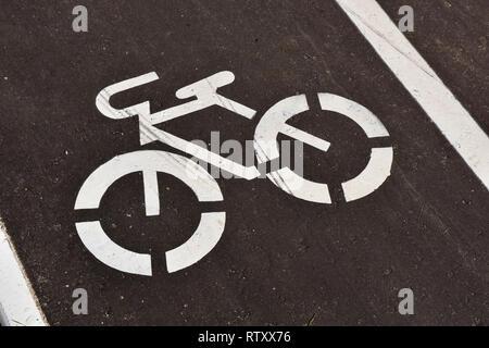 Weiß Fahrrad Schild auf eine asphaltierte Straße. - Stockfoto