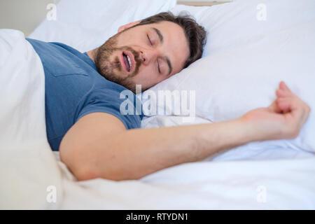 Müde Mann schlafen und laut schnarchend im Bett - Stockfoto