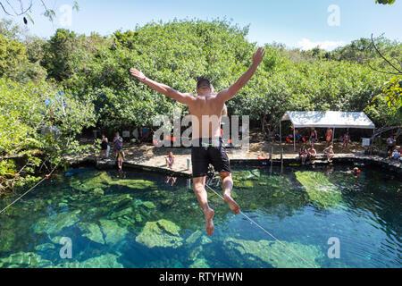 Mann springt von einer Klippe in die cristalino Cenote in Mexiko.