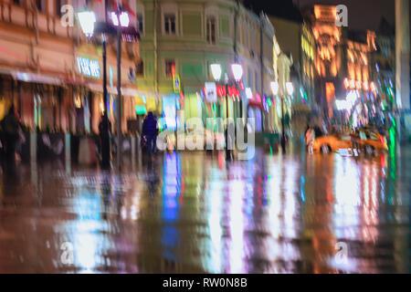 Beeilen, um jungen Menschen unter Sonnenschirmen an einem regnerischen Nacht in der Straße der Stadt. Brillante Ausleuchtung von Laternen und Schaufenstern. Konzept der Jahreszeiten - Stockfoto
