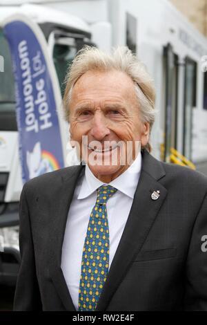 Derek Bell MBE, der äußerst erfolgreichen Rennfahrer, mit einem der Nächstenliebe Mobile Cancer Care Units, außerhalb der Kathedrale von Gloucester für die s geparkt - Stockfoto
