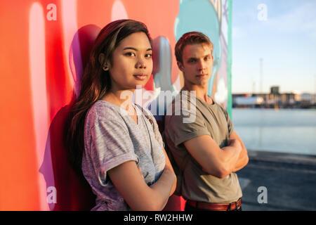 Cool junges Paar stehend durch Graffiti in der Stadt - Stockfoto