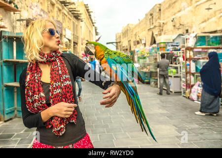 Glückliche Frau Küsse ein Papagei an Vogel Souq in Souq Waqif, den alten Markt und Touristenattraktion in Al Souq, Doha City Centre, Katar - Stockfoto