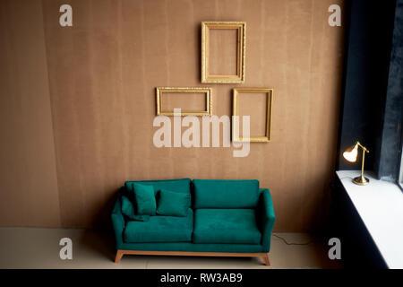 Emerald samt retro Sofa gegen einen warmen braunen Wand. Das Innere eines stilvollen Zimmer. Leere gold Frames an der Wand. - Stockfoto