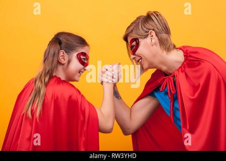 Mutter und Tochter gekleidet wie Superhelden spielen Arm Wrestling auf gelben Hintergrund. Super Mom. Super Tochter. Roten Cape. Rote Maske. Parenting. - Stockfoto