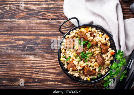 Bulgur mit Fleisch und Gemüse auf hölzernen Tisch - Stockfoto