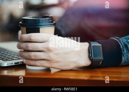 Nahaufnahme des Menschen Hände mit modernen elektronischen Uhren und Laptop Kaffee trinken in der modernen hellen Café bei Business Lunch. Freiberufler oder Unternehmer nicht - Stockfoto