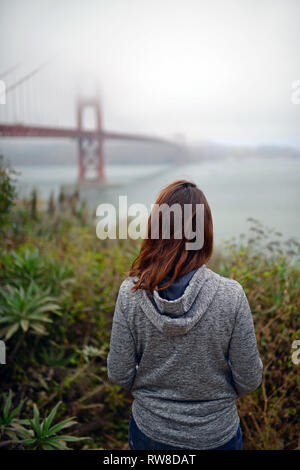Junge Frau, die an der Golden Gate Bridge, San Francisco. - Stockfoto