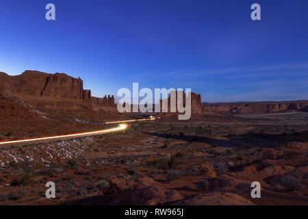 Dämmerung lange Belichtung mit Scheinwerfern als helle gelbe Linien markieren die Kurven und Straße von der Straße Eingabe der Arches National Park - Stockfoto