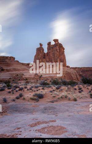 Giant Red Rock verfügen als die Drei Klatschbasen im Arches National Park, Foto takin mit einer sehr langsamen shuttterpeed das sich schnell bewegende Wolken zu verwischen bekannt - Stockfoto