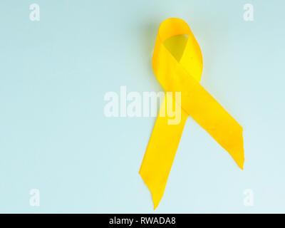 Childhood Cancer Awareness Ribbon Gelb auf blauem Hintergrund. Krebs im Kindesalter. - Stockfoto