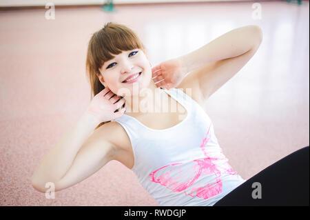 Frau tun stretching-Übungen auf dem Boden in der Turnhalle - Stockfoto
