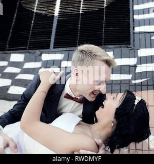 Der Bräutigam seine Braut Umarmungen auf der Straße - Stockfoto