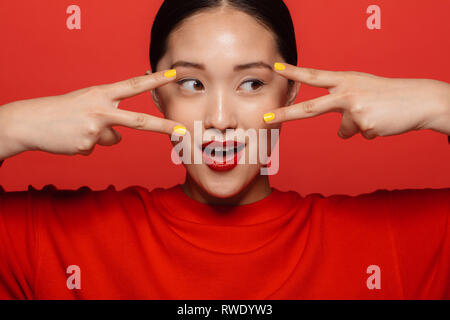 Close up Portrait von jungen asiatischen Frau mit schönen Make-up durch die Finger auf rotem Hintergrund. - Stockfoto