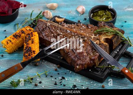 T-bone Rindfleisch Anteil serviert auf einem Schneidebrett mit Saucen, Rosmarin, Mais Grill - Stockfoto