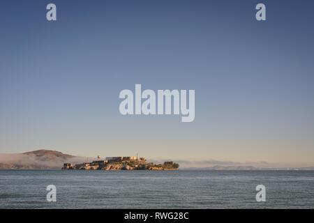 Alcatraz angesehen vom Ufer aus mit Nebel über dem Wasser im Hintergrund - Stockfoto