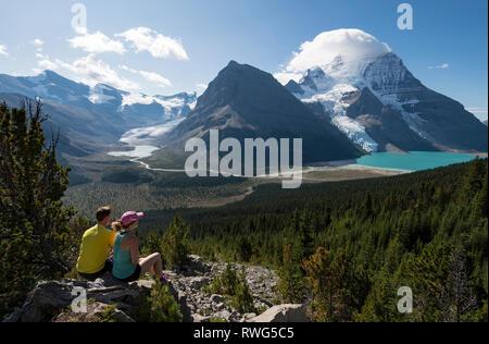 Ein junger Mann und eine Frau, die Ruhe und die Aussicht auf den Mumm Grundlage Trail mit Mt. Robson und Nachhut Berg im Hintergrund, Mt. Robson Provin - Stockfoto